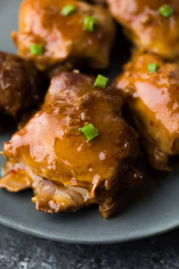 close up shot of sticky honey garlic chicken thighs on gray plate