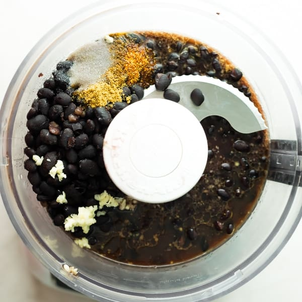 black beans in a food processor with black bean hummus ingredients