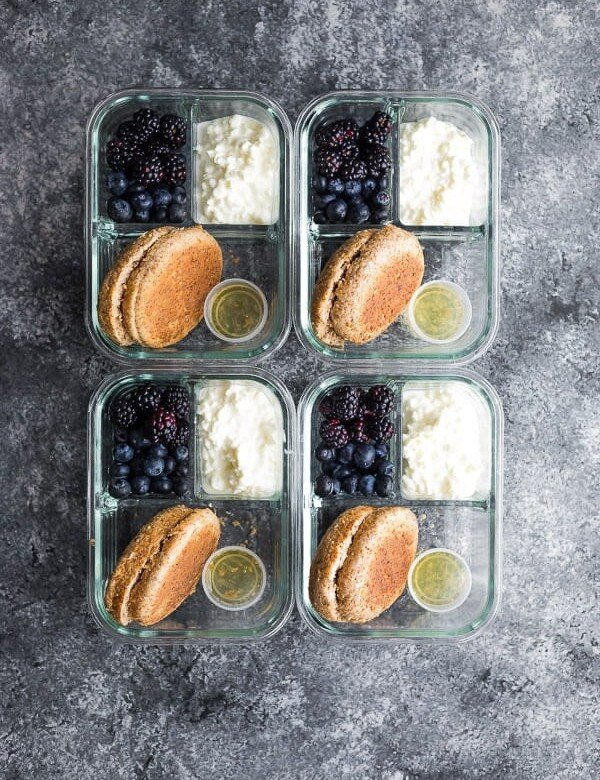 overhead shot of four english muffin breakfast bento boxes on gray background