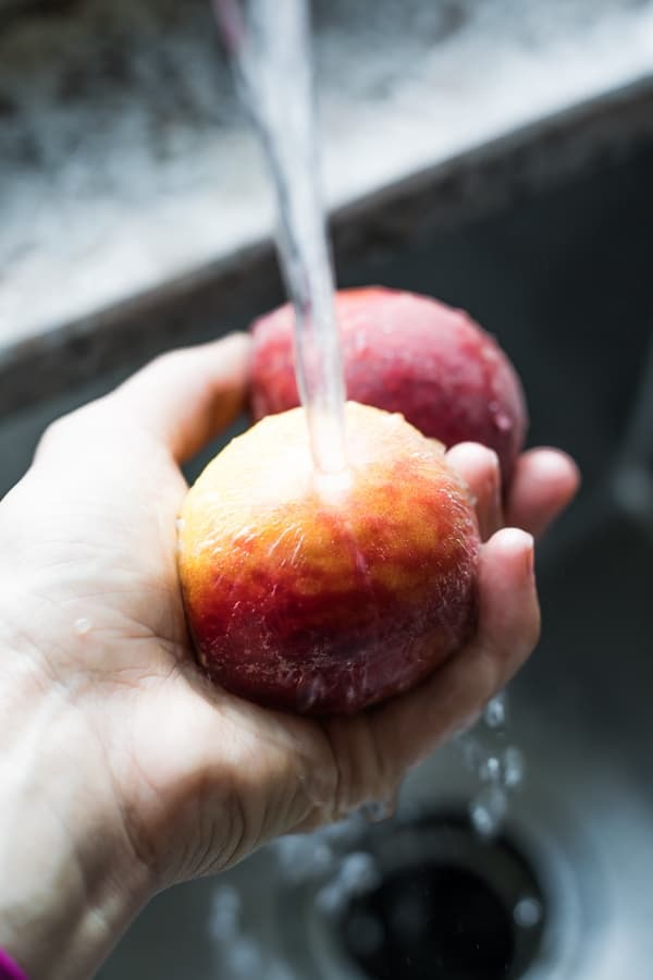 How to Freeze Peaches: washing peaches under tap