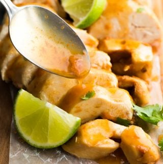 Close up shot of chipotle lime chicken breasts with a spoon drizzling sauce on top and fresh lime wedges