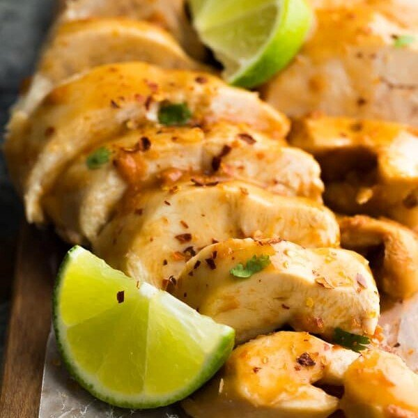 close up shot of chipotle lime chicken breasts sliced with lime wedges