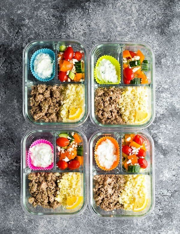 overhead shot of four meal prep containers with greek turkey and salad