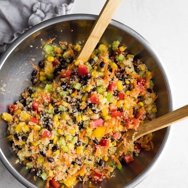 Quinoa Black Bean Salad in a large bowl with two wooden tongs