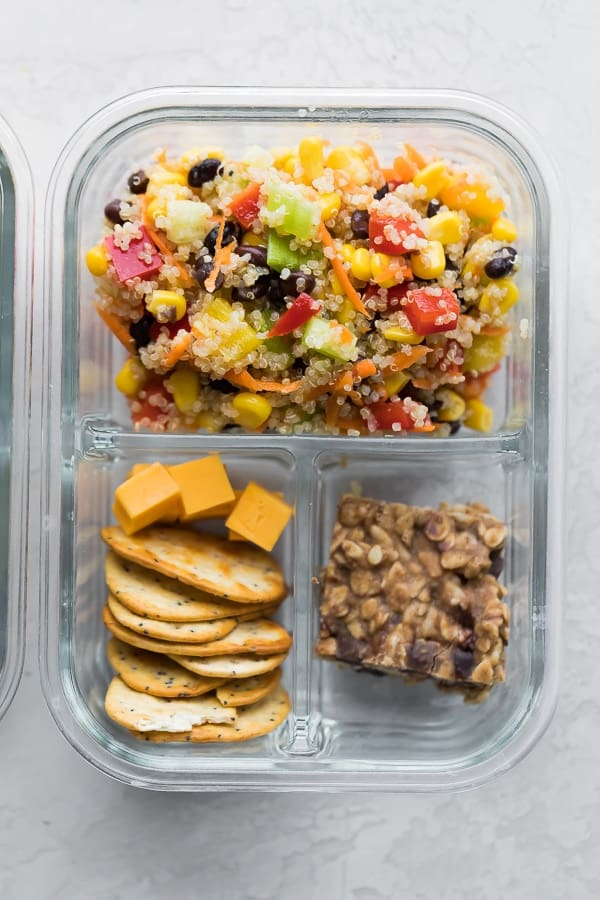 quinoa black bean salad in meal prep container with snack bar and crackers