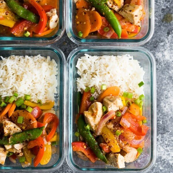 overhead shot of four coconut sweet chili chicken stir fry bowls in glass meal prep containers
