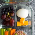 tuna protein bistro box in glass meal prep container including grapes, egg, cheese, and veggie sticks