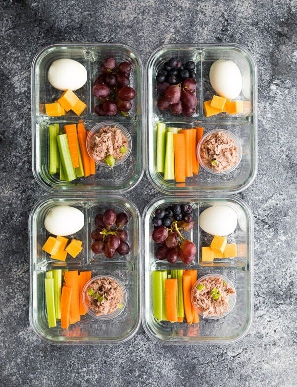 overhead shot of four tuna protein bistro boxes including grapes, egg, cheese, and veggie sticks