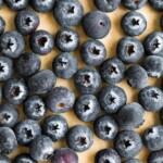 overhead shot of lots of blueberries on wood cutting board