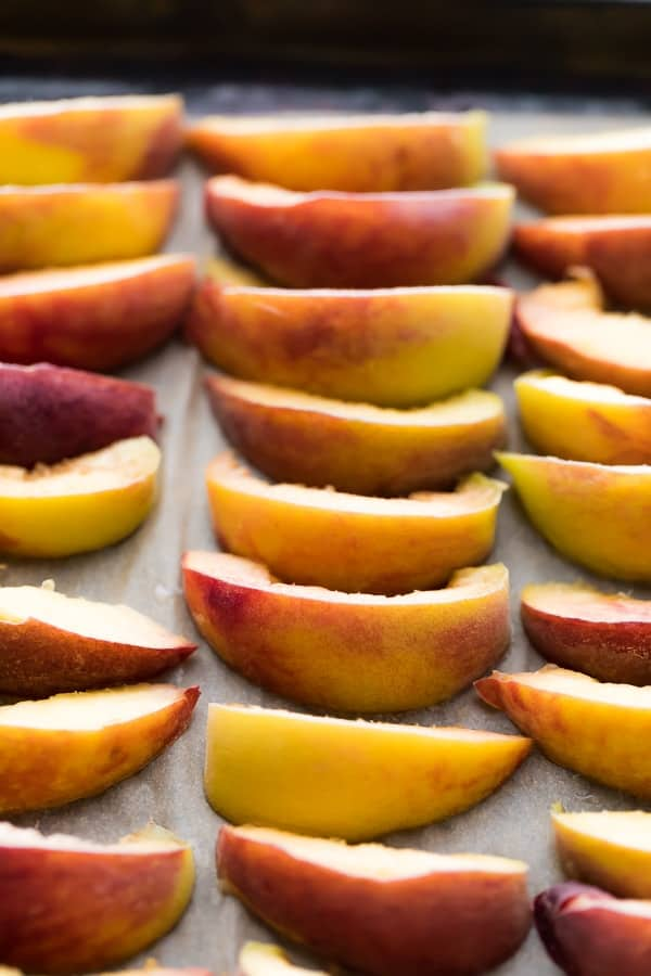 How to Freeze Peaches: peaches sliced and arranged on baking sheet