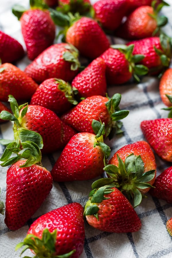 strawberries laid out on a white and blue dish towel