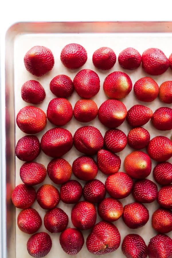 how to freeze strawberries: berries lined up on baking sheet
