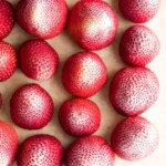 overhead shot of frozen strawberries on wood cutting board