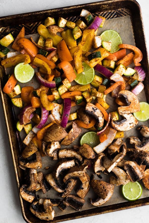 portobello mushrooms, zucchini, red onion, and lime wedges on sheet pan