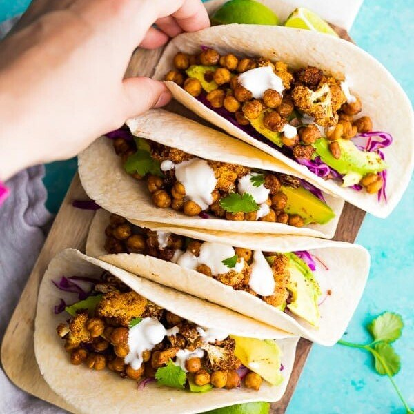 four air fryer cauliflower chickpea tacos lined up on blue background with hand grabbing one
