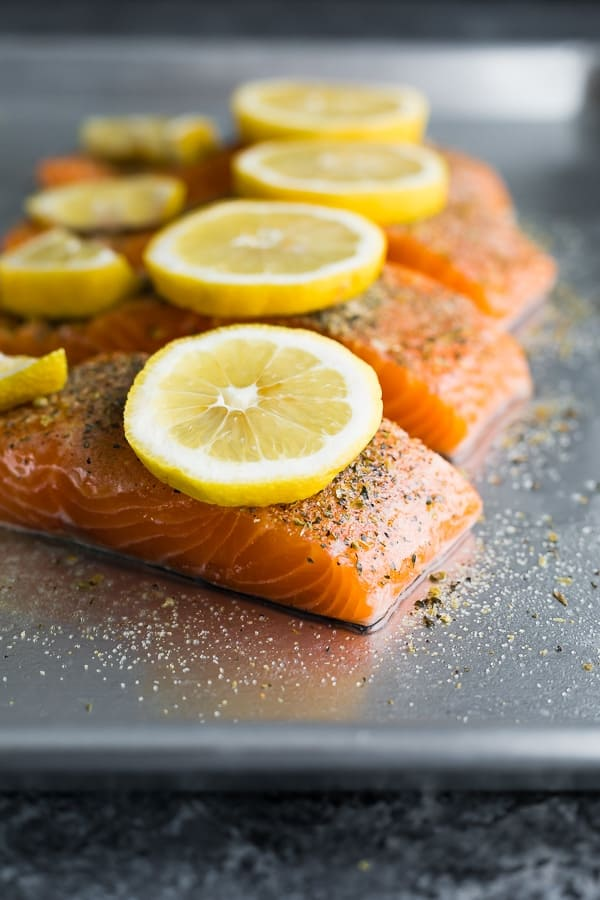 how to cook salmon in the oven- showing salmon fillets with seasoning and lemon wedgest ready to go into the oven