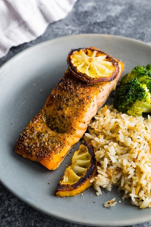 herb crusted broiled salmon on plate with rice, charred lemons and broccoli