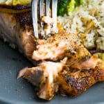 Close up shot of herb crusted broiled salmon being flaked with a fork