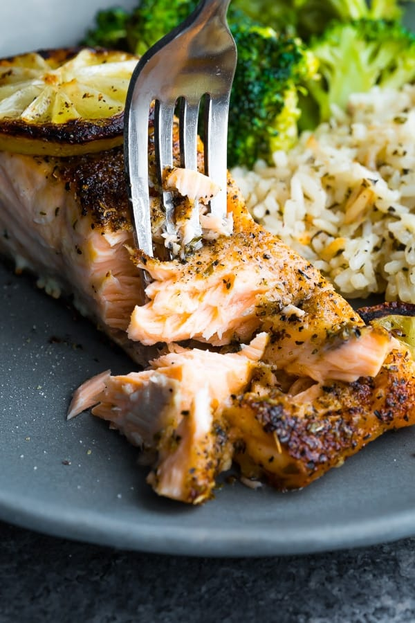Close up of a fork flaking the cooked broiled Salmon