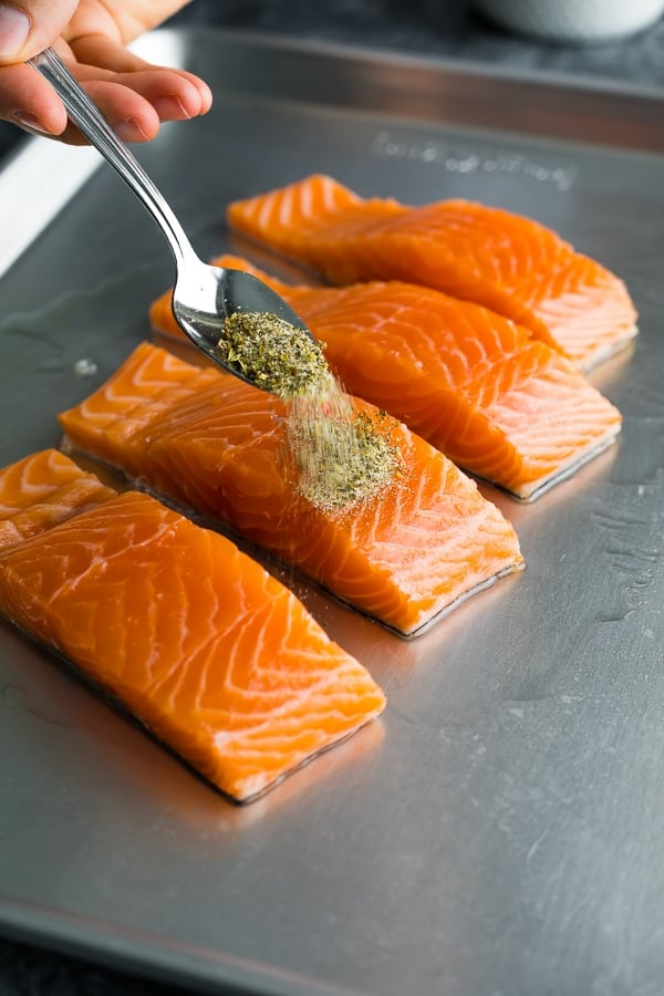 Sprinkling herbs onto salmon on a sheet pan