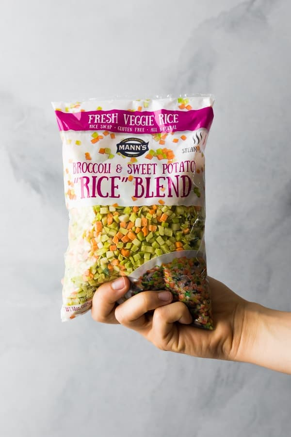 hand holding up bag of Mann's Broccoli and sweet potato rice blend