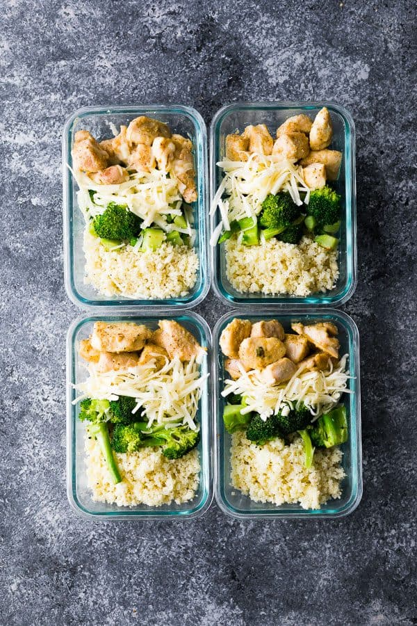 overhead shot of four glass containers with cheesy chicken rice and broccoli bowls