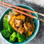overhead shot of teriyaki chicken with broccoli in blue bowl and chopsticks