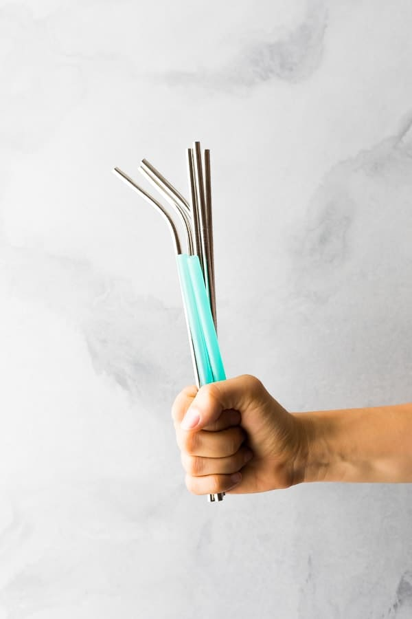 hand holding up multiple stainless steel straws