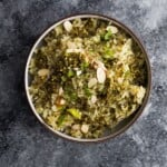 overhead shot of pesto green rice in brown bowl on gray background
