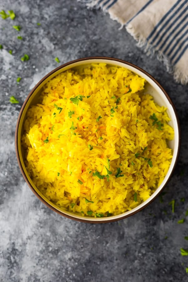 saffron rice in brown bowl with green herbs sprinkled on top