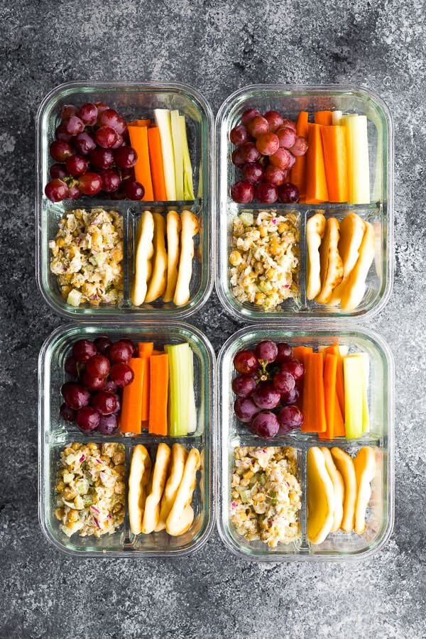 overhead shot of four meal prep containers with chickpea salad bento