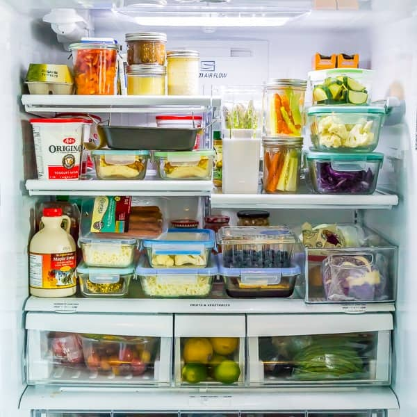 open refrigerator with a variety of foods and glass meal prep containers