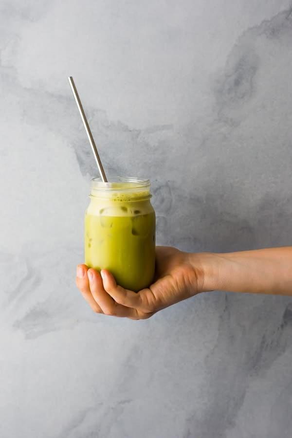 hand holding iced matcha latte