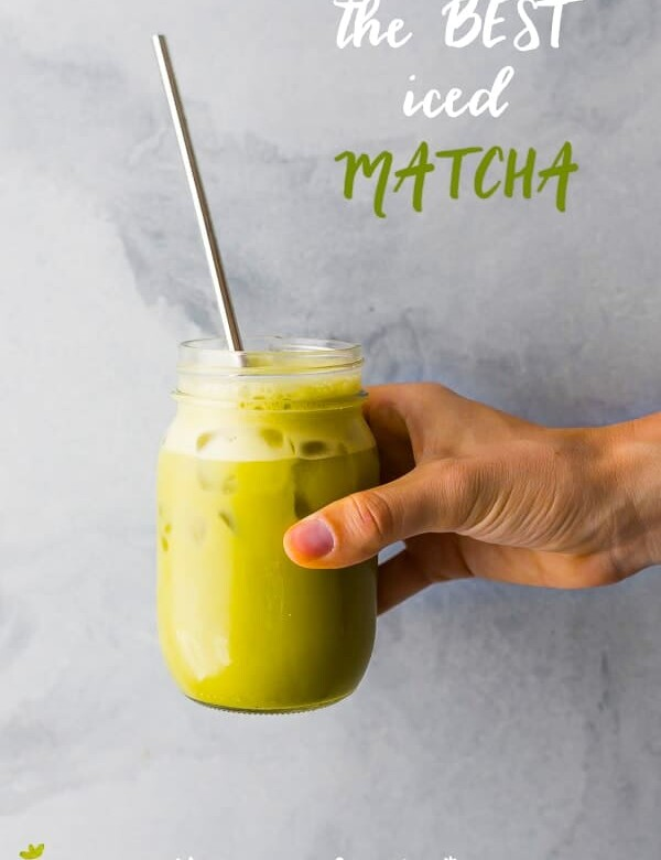 hand holding an iced matcha latte with straw