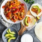 Overhead view of chicken fajitas in large white bowl with side of avocado slices, sour cream, tortillas, and wood cutting board