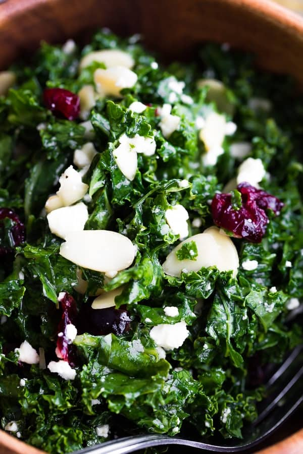close up shot of the staple kale salad recipe with feta, almonds and cranberries