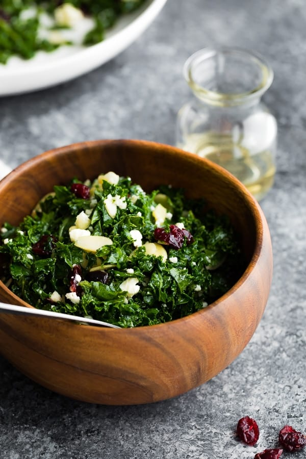 kale salad with cranberries in wooden bowl
