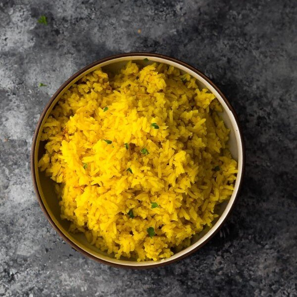 overhead shot of turmeric yellow rice in bowl on gray background