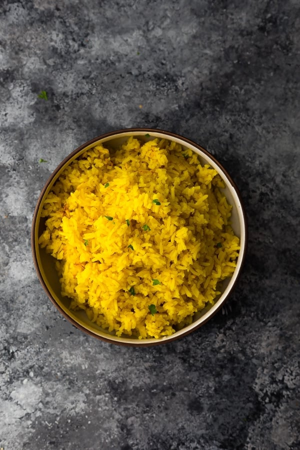 bowl with turmeric yellow rice on grey background