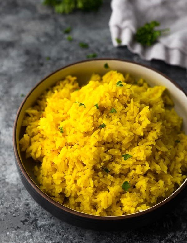 side view of turmeric yellow rice in black bowl