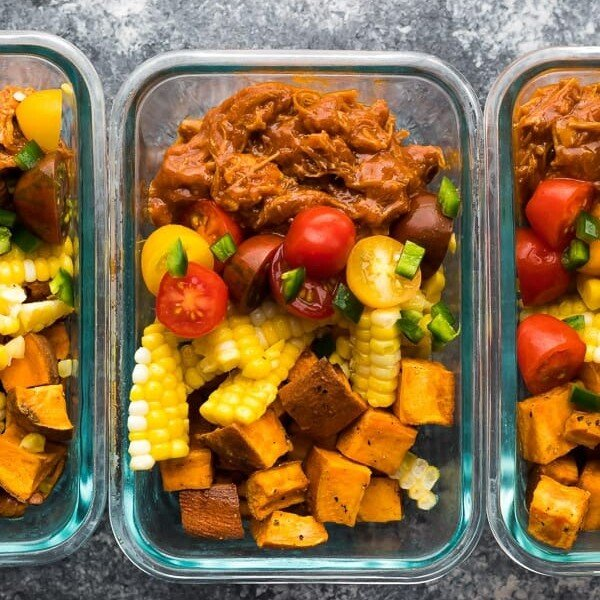 overhead shot of pulled pork meal prep bowls in glass containers
