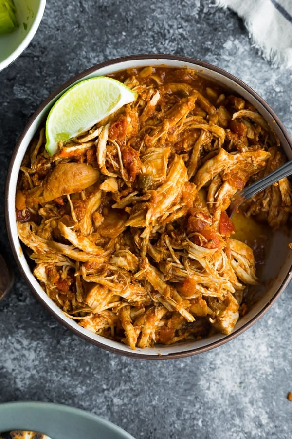 crockpot chicken and salsa in bowl on grey background