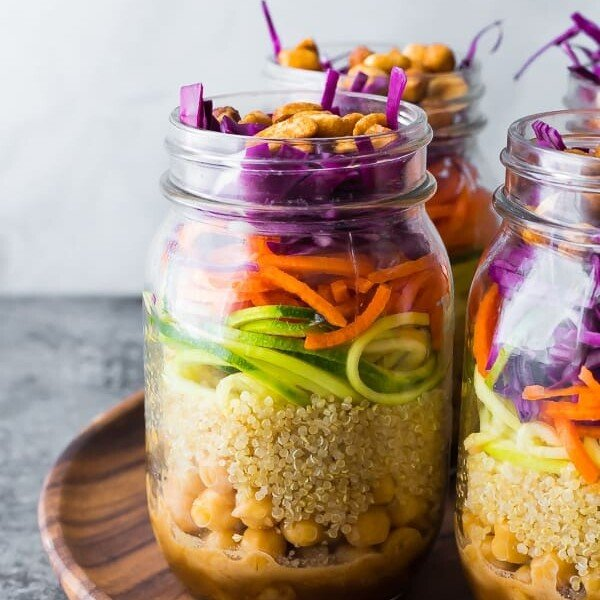 Close up shot of mason jars filled with thai chickpea mason jar salad on wood tray