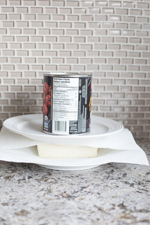 Side view of tofu on a white plate with a paper towel on it and a can sitting on top of the plate to drain tofu