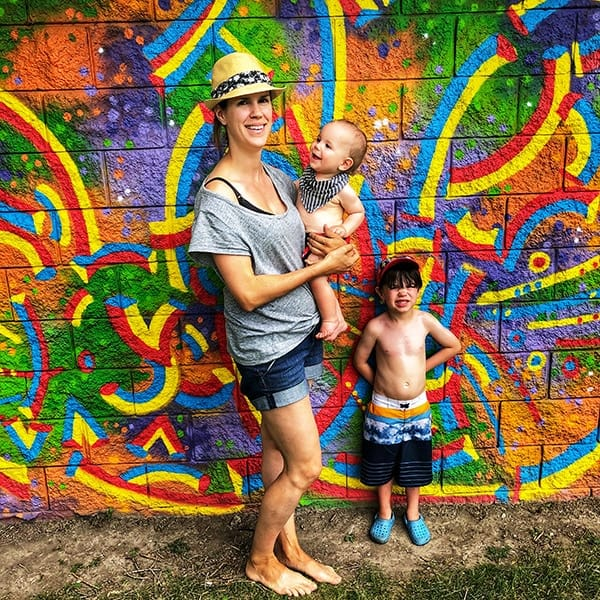 Denise with her two kids in front of a mural wall