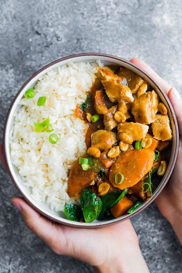 overhead shot of hands holding bowl filled with asian peanut chicken and rice