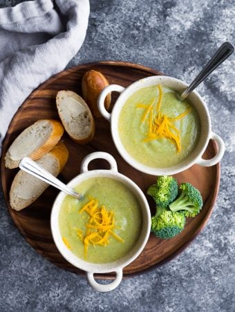 overhead shot of healthy broccoli cheese soup in two white bowls with fresh bread, cheese and broccoli on wood tray