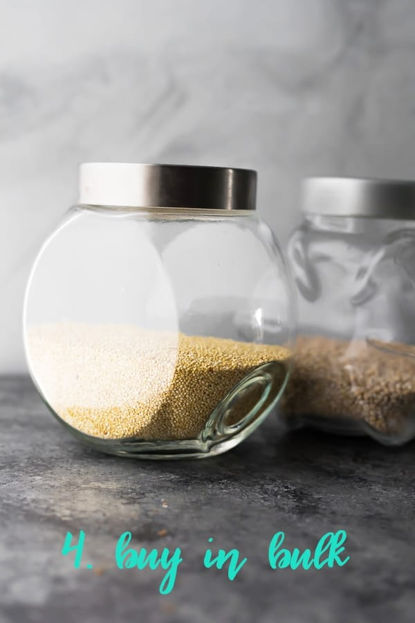 close up shot of grains in a glass jar with text buy in bulk