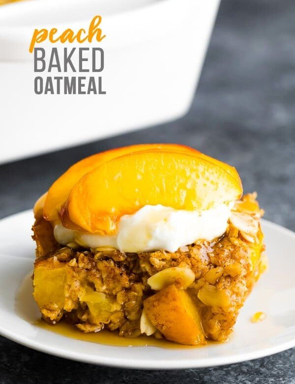 side view of peach baked oatmeal on a white plate with fresh peaches on top