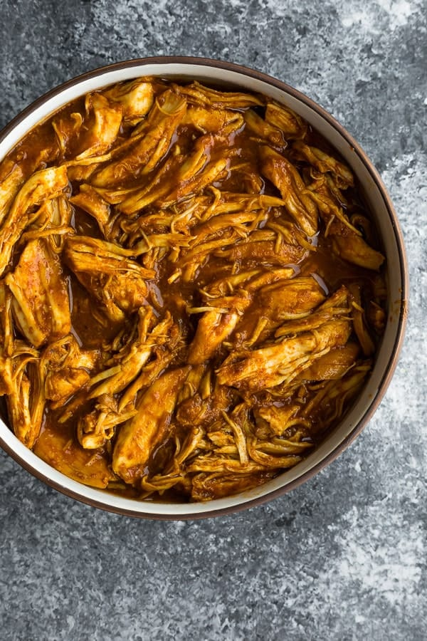 overhead shot of a bowl of bbq pulled chicken slow cooker on a grey background